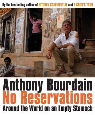Book cover image: Bourdain sitting on a stoop with a wall of posters and doorways behind hi, and two men standing and sitting nearby